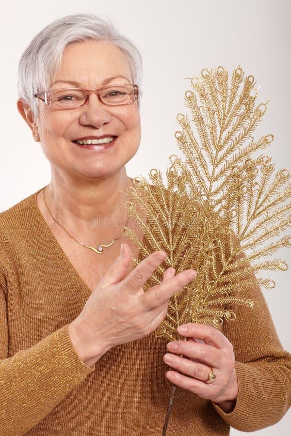 Dame pluse âgé avec le sourire d'or de fan de branche photo libre de droits