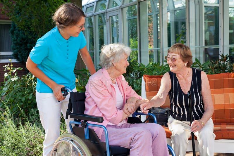 Dame pluse âgé avec un soignant parlant à un ami photos libres de droits