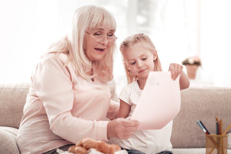 Dame pluse âgé blonde dans des lunettes semblant amusées photographie stock libre de droits