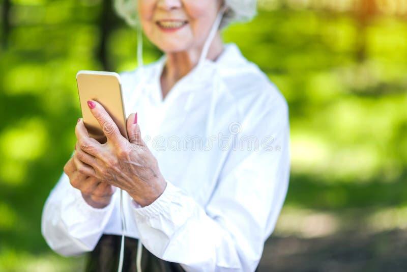 Dame pluse âgé heureuse à l'aide du téléphone portable tout en s'exerçant dehors photos stock