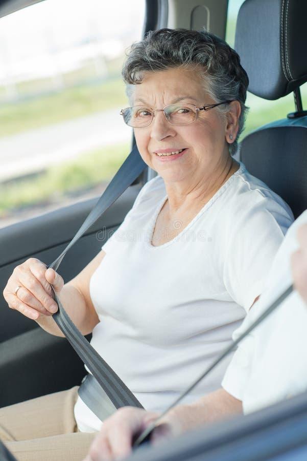 Dame pluse âgé mettant sur la ceinture de sécurité photo stock