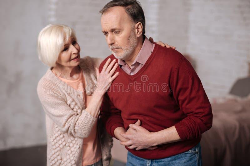 Dame pluse âgé soutenant son mari avec le mal de ventre images stock