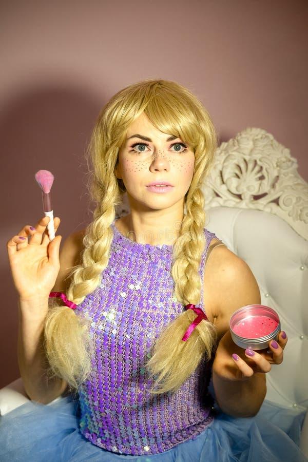 Dame in Puppenkomben macht Make-up, Blush lizenzfreie stockbilder