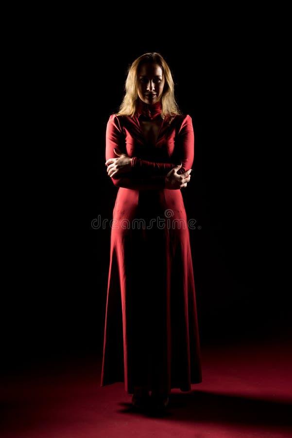 Dame in rode toga die en zich in studio bevinden stellen Portret van mooie elegante vrouw in avondjurk stock foto's