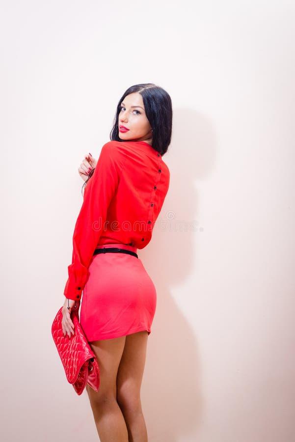 Dame in rood: mooie, verleidende donkerbruine vrouw in rode kleding met handtas status die camera over schouder bekijken royalty-vrije stock foto