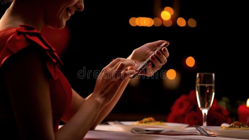 Dame séduisante mettant en rouleau l'appli de smartphone dans le restaurant, homme de attente, rendez-vous avec une personne inco photographie stock