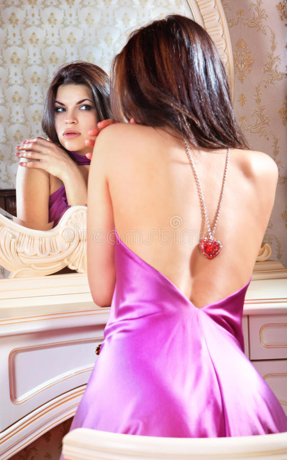 Dame schaut in einem Spiegel lizenzfreie stockfotos