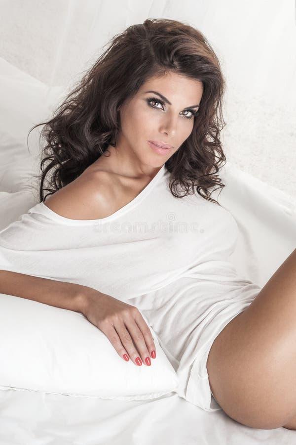 Dame sensuelle de brune posant dans le lit photographie stock libre de droits
