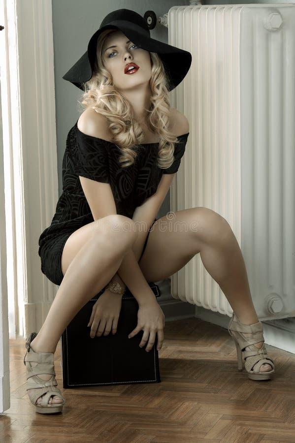 Dame sensuelle posant dans la robe noire et le chapeau énorme photographie stock