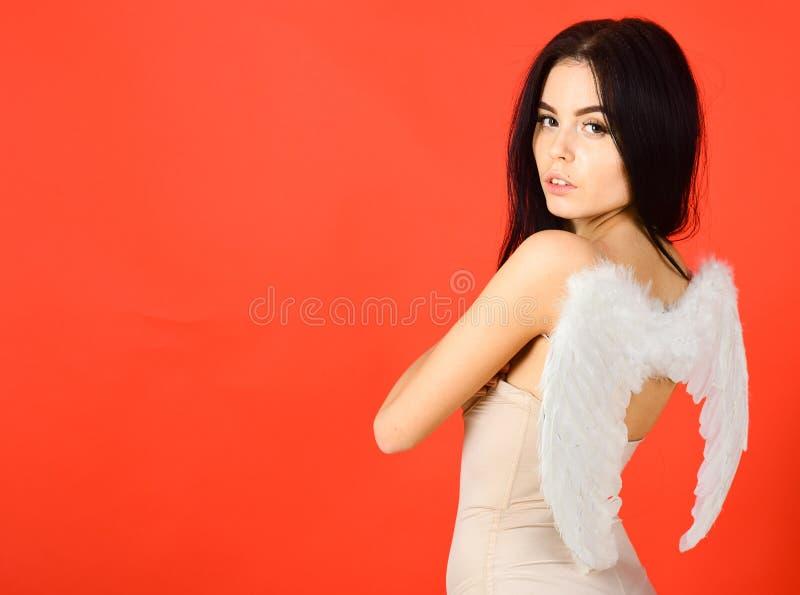 Dame sexi gekleidet als Engel, roter Hintergrund Sexy Engelskonzept Frau auf nachdenklichem Gesichtsspiel-Rollenspiel Mädchen in  stockbilder