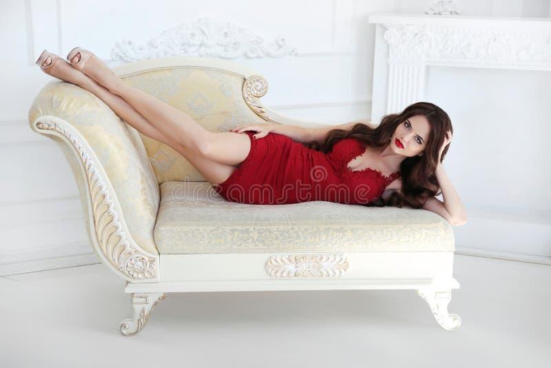 Dame sexy de belle brune dans la robe rouge se trouvant sur le sofa moderne photos stock
