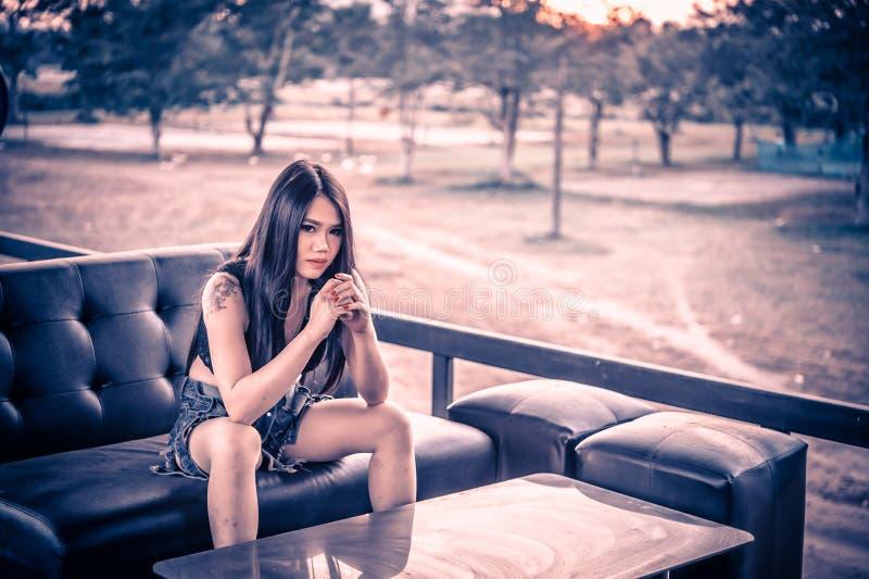 Dame sexy de l'Asie dans la chemise noire et des jeans courts photos stock