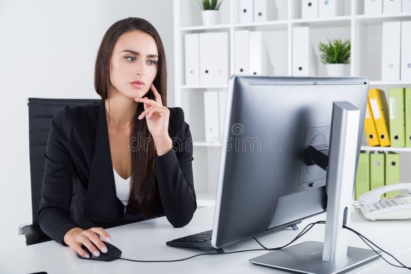 Dame songeuse d'affaires et son ordinateur photos libres de droits