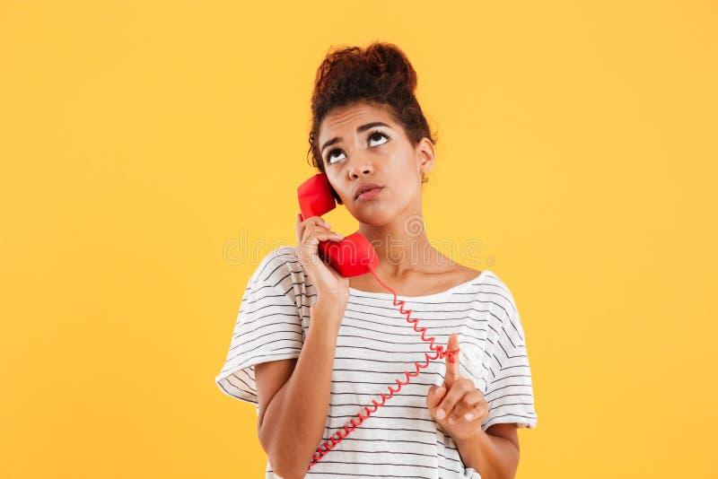 Dame songeuse réfléchie parlant au téléphone rouge d'isolement photo stock