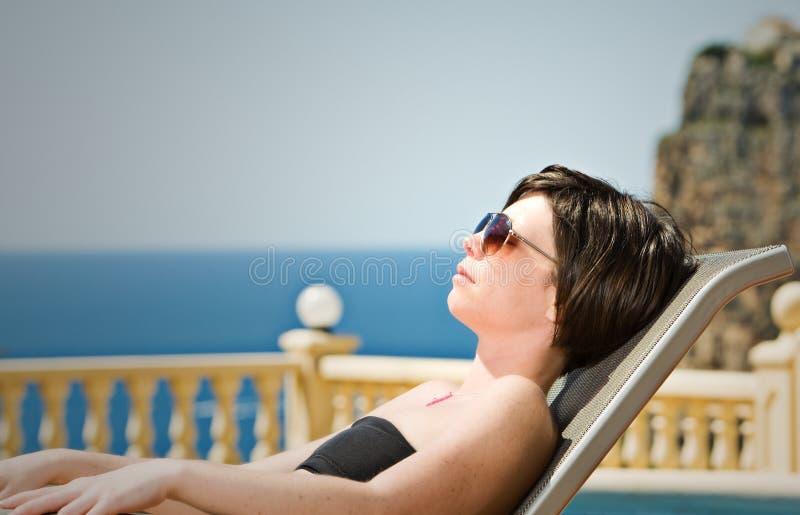 Dame Sunbathing mit Mittelmeerhintergrund lizenzfreies stockfoto