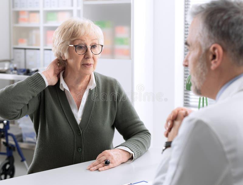Dame supérieure avec douleur cervicale dans le bureau du docteur photos libres de droits