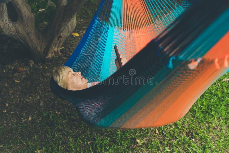Dame supérieure détendant dans un hamac photographie stock