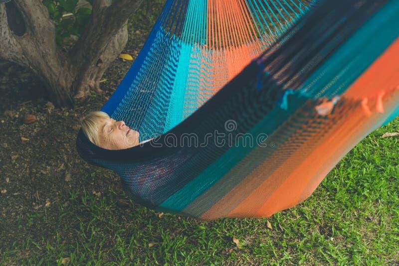 Dame supérieure détendant dans un hamac images stock