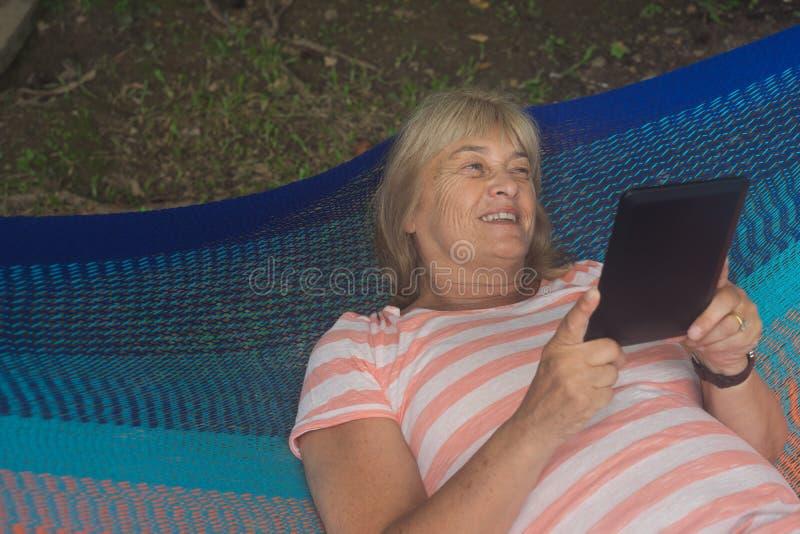 Dame supérieure détendant dans un hamac photos libres de droits