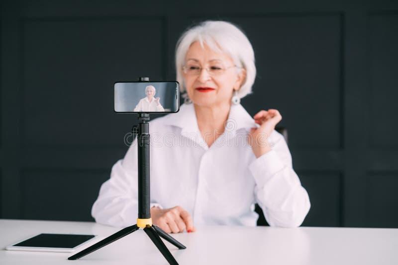 Dame supérieure d'affaires bloguant pour tirer la vidéo mobile photographie stock libre de droits