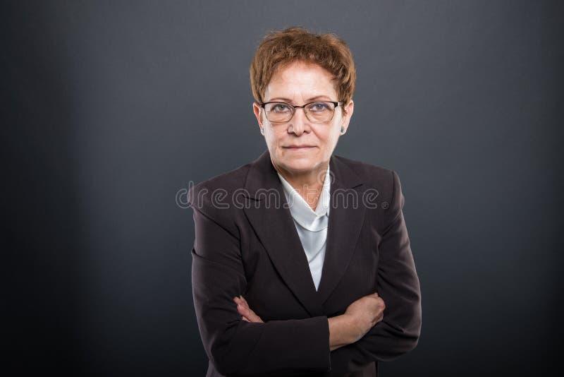 Dame supérieure d'affaires posant avec des bras croisés image libre de droits