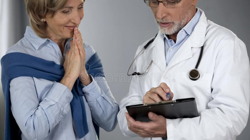 Dame supérieure heureuse d'entendre des résultats de traitement, docteur disant de bonnes nouvelles, progrès photo stock