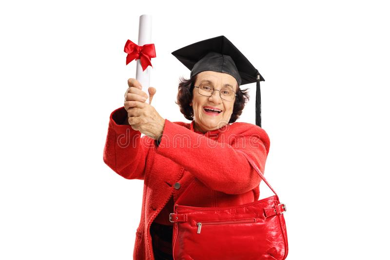 Dame supérieure joyeuse avec un diplôme et un chapeau d'obtention du diplôme photo stock