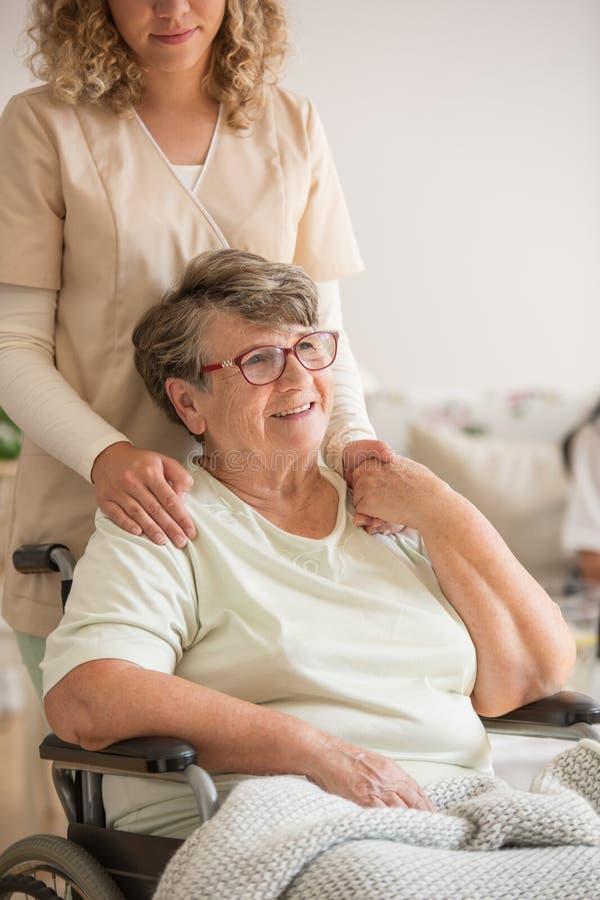 Dame supérieure sur le fauteuil roulant avec le jeune volontaire dans l'uniforme beige la soutenant photos libres de droits