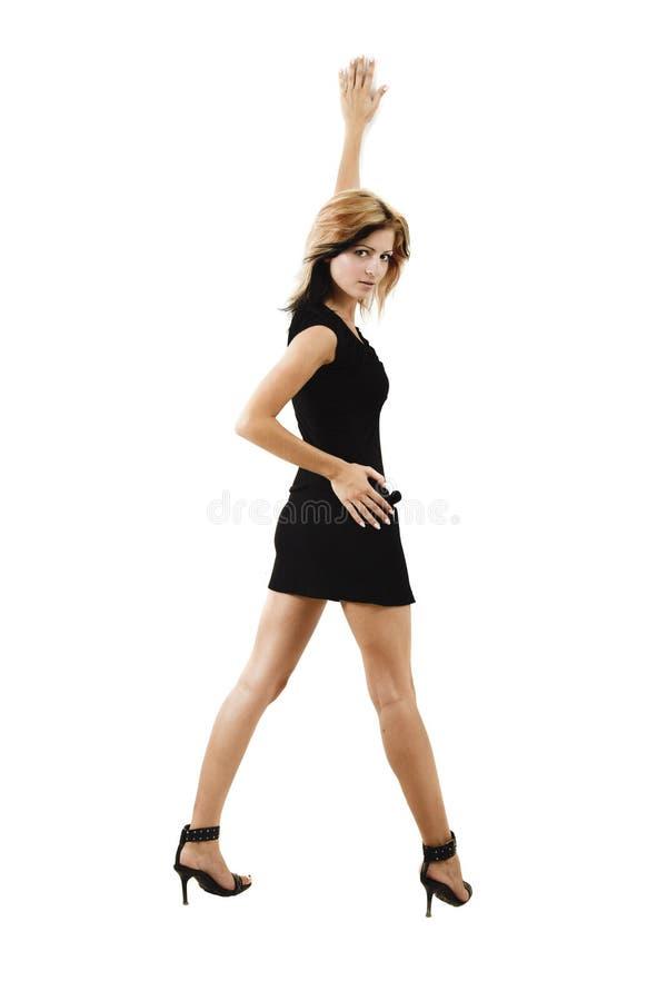 Dame in zwarte over witte achtergrond die bij de muur leunt stock foto's