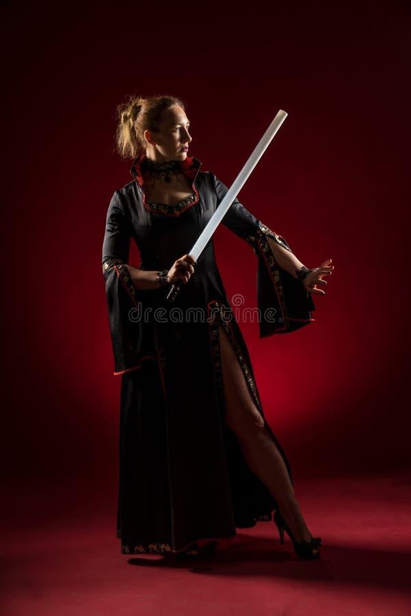Dame in zwarte toga met een zwaard die en zich in studio bevinden stellen Portret van mooie elegante vrouw in avondjurk stock fotografie