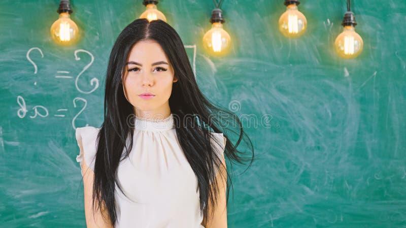 Dameleraar op kalme gezichtstribunes voor bord Vrouw met lang haar in witte blousetribunes in klaslokaal slim stock foto's