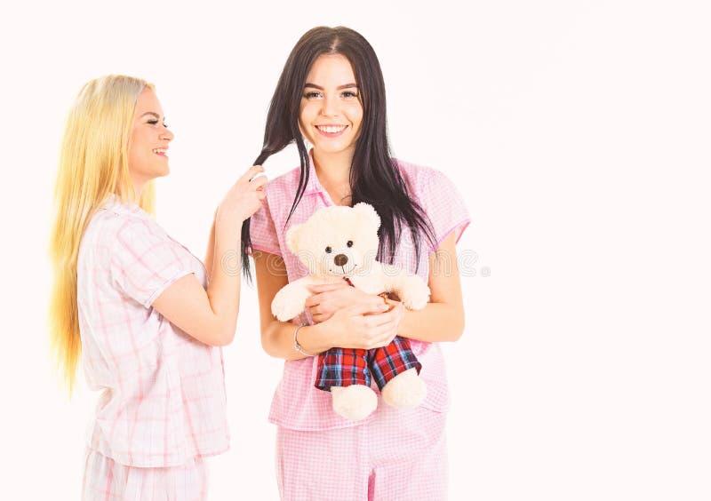 Damen auf lächelnden Gesichtern mit Plüschspielzeugbären schauen nett Mädchenhaftes Freizeitkonzept Mädchen in den rosa Pyjamas,  stockfotografie
