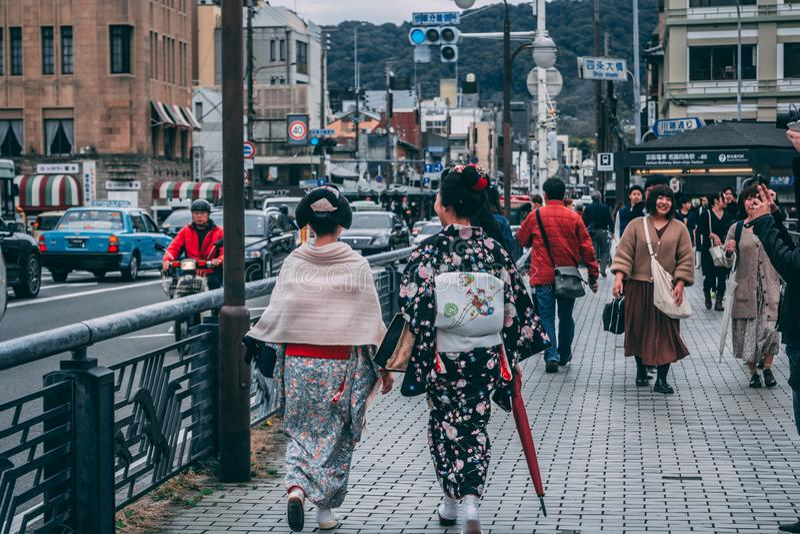 Damen in den traditionellen japanischen Ausstattungen die Kyoto-Straßen gehend stockbilder