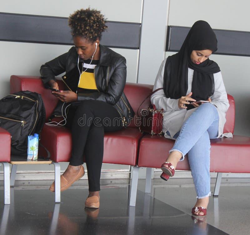 Damen, die intelligentes Telefon warten stockfotografie