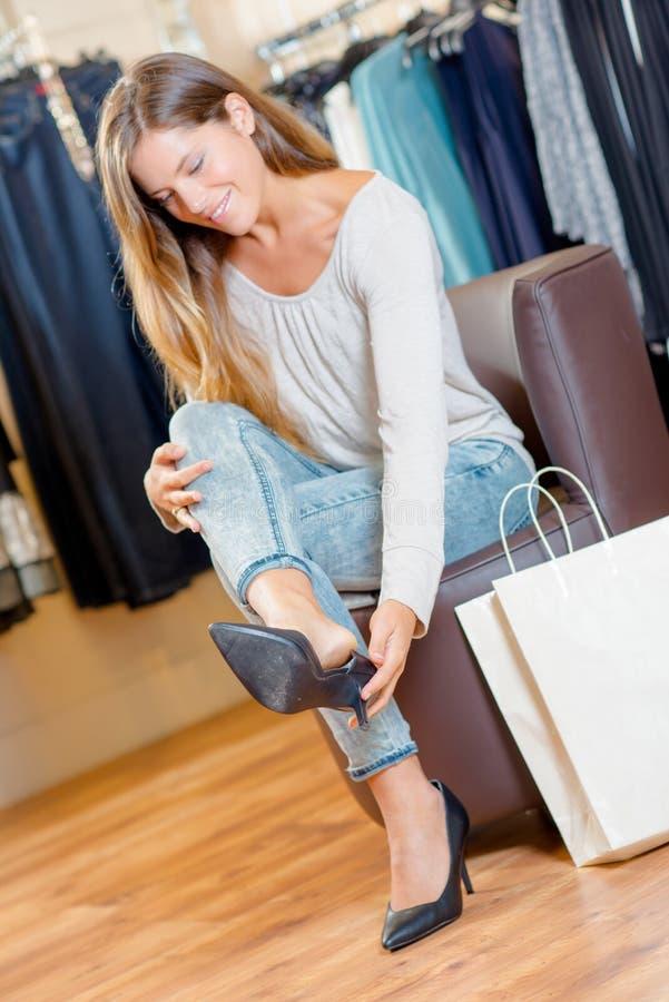 Damen i kläder shoppar att försöka på skor arkivbilder