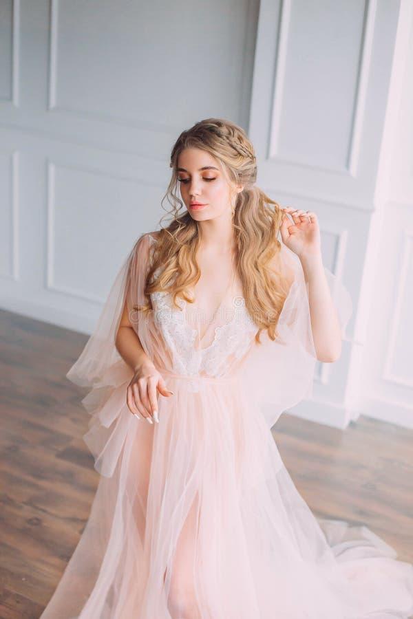 Damen i rosa lyxig ljus klänning i rymligt rum med vita väggar och ljust ljus som är försiktiga snör åt peignoir och skyler royaltyfri fotografi