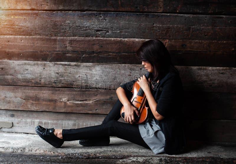 Damen i svart dräkt sitter på grungeyttersidabottenvåningen, hållfiol med pilbågen i armar, vändframsida ner till fiolen, tappnin royaltyfria bilder