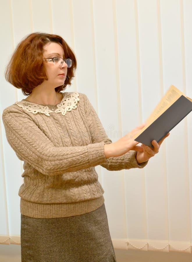 Damen läser boken på en utsträckt arm över exponeringsglas arkivbild