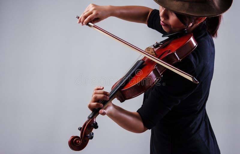 Damen med den svarta dräkten och hatten för kläder som bruna spelar fiolen fotografering för bildbyråer