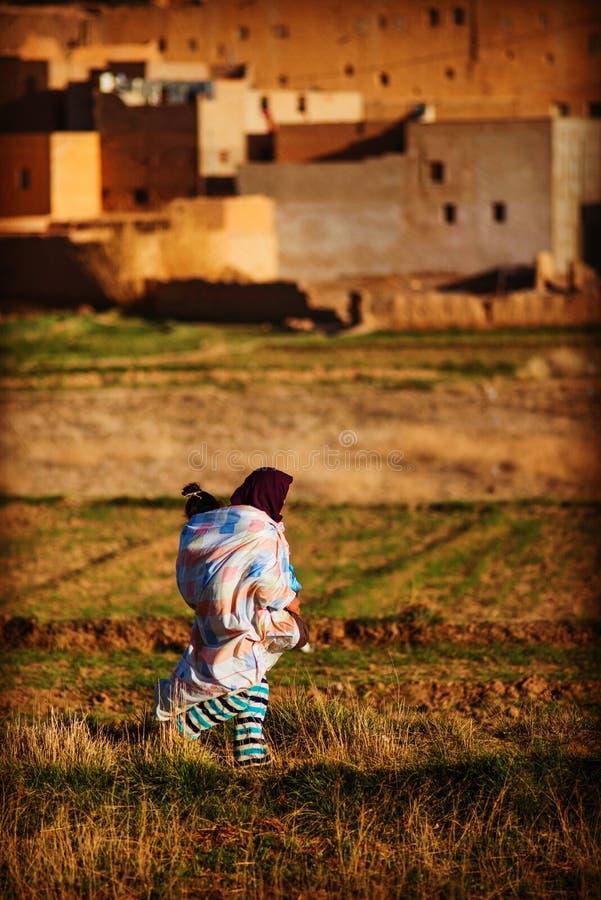 Damen och barnet för fattig muslin går den gamla i den gamla traditionella Marocko araben Medina och by arkivbild