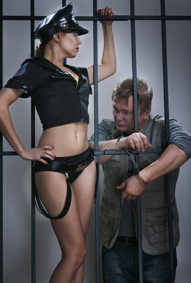 Damen-Polizeibeamte schützt den Straftäter im Gefängnis stockbilder