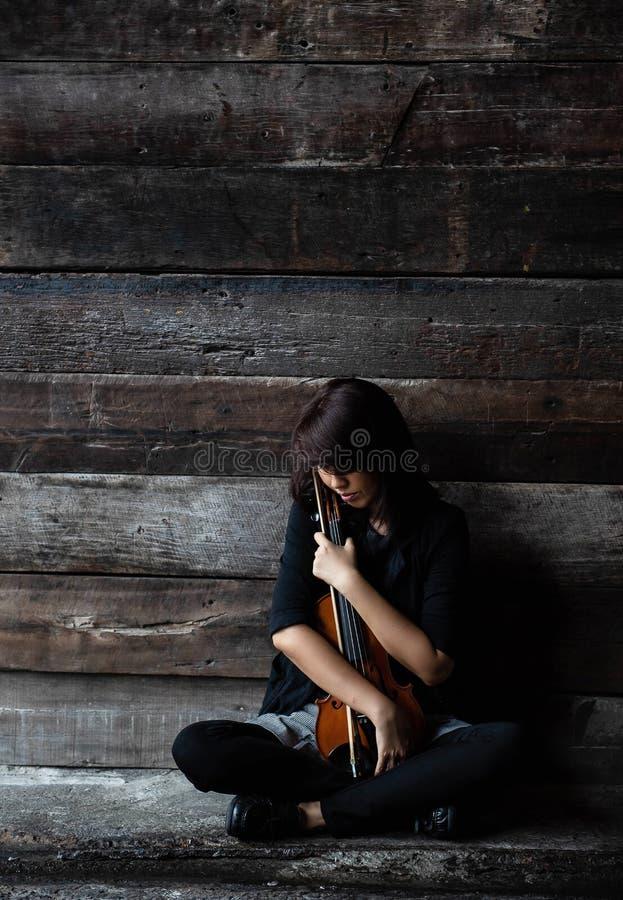 Damen sitter på golv för grungeyttersidacement, hållfiolen och pilbågen i hennes armar, vändframsidan ner till fiol-, tappning- o royaltyfri bild