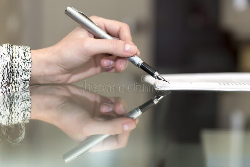Damen undertecknar det formella dokumentet royaltyfri fotografi