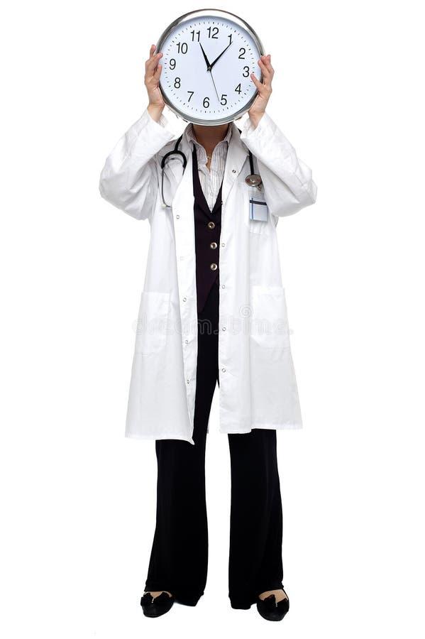 Damendoktor, der Borduhr vor ihrem Gesicht anhält stockbilder