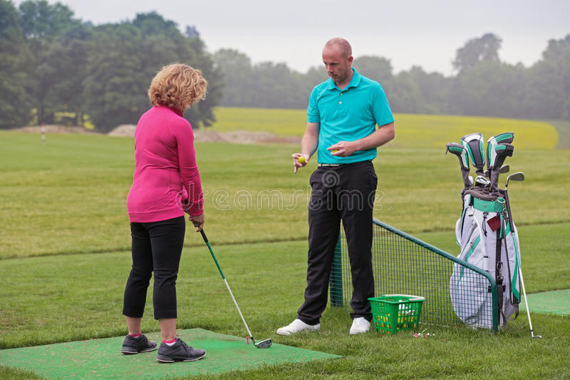 Damengolfspieler, der durch ein Golfpro unterrichtet wird. lizenzfreies stockfoto