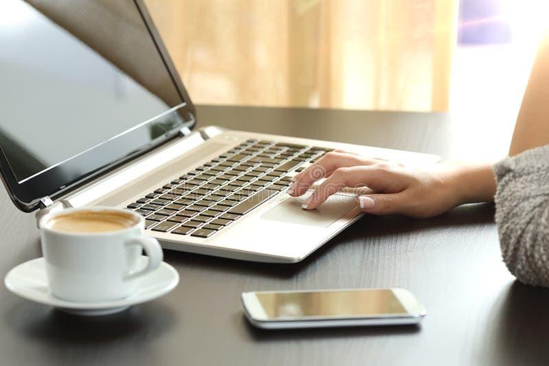 Damenhand, die zu Hause einen Laptop grast stockfotos
