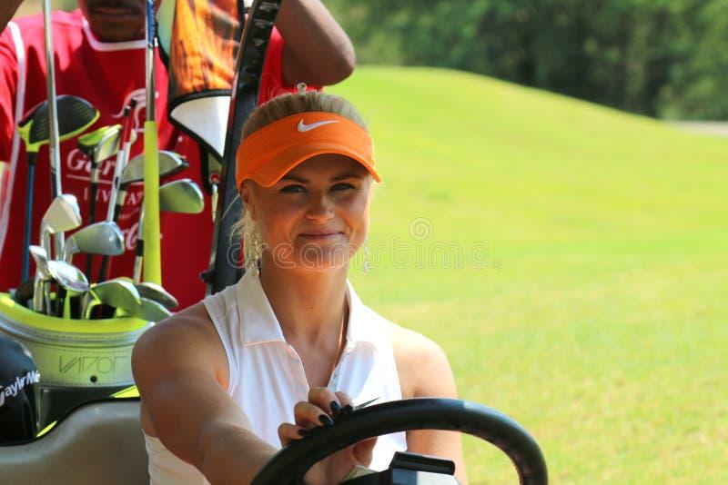Damenprogolfspieler Carly Booth hinter Lenkrad des Golfmobils lizenzfreies stockfoto