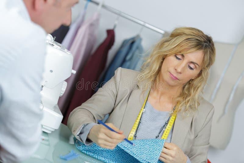 Damenschneiderin bei der Arbeit, die Mustergewebe macht lizenzfreies stockbild
