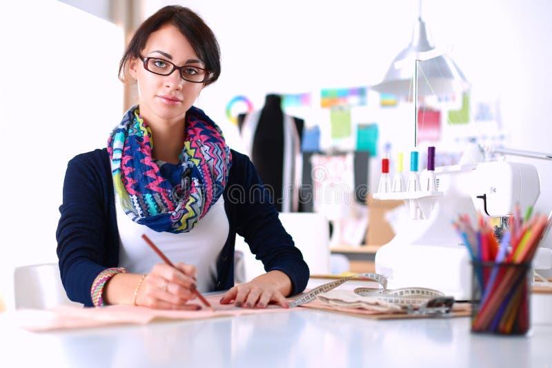 Damenschneiderin, die Kleidungsmuster auf Papier entwirft stockbilder