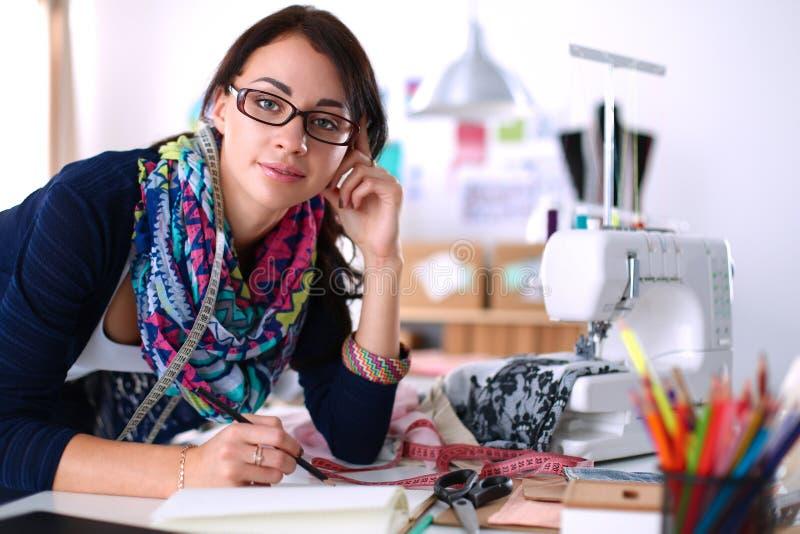 Damenschneiderin, die Kleidungsmuster auf Papier entwirft stockbild